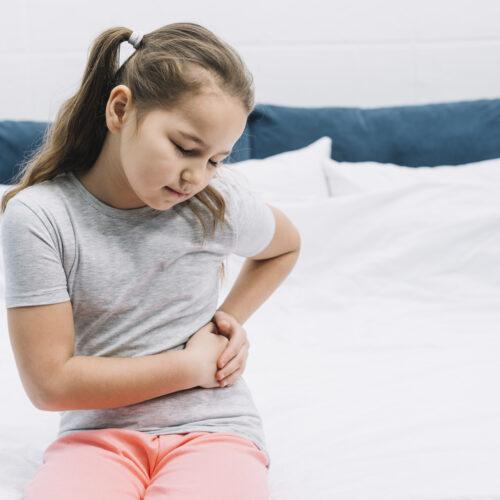 girl-sitting-bed-having-abdominal-pain
